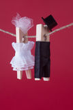 Peg characters on pink red background. Bride in white dress and groom character man suit hat. Love concept photo. Macro Stock Photos