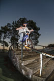 Peg grind. Biker doing peg grind down the hand rail over the stairs Stock Images