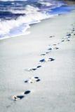 Pegadas de Cuba na areia das caraíbas com ondas Imagens de Stock