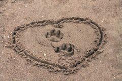 Pegadas do cão no coração pintado interior da areia imagem de stock royalty free