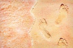 Pegadas dos povos em uma areia colorido nas ondas macias da costa de mar da cor cor-de-rosa Fotografia de Stock