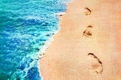 Pegadas dos povos em uma areia cor-de-rosa dourada nas ondas macias da costa de mar da cor azul e verde Cl criativo marinho do fu Foto de Stock