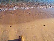 Pegadas e castelo pequeno na praia vazia - ondas pequenas calmas da areia imagens de stock royalty free
