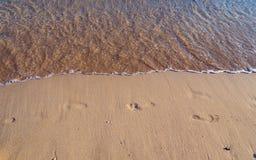 Pegadas em um Sandy Beach vazio - aproximação pequena das ondas fotografia de stock royalty free