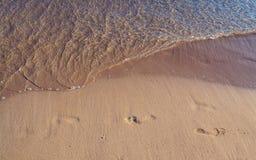 Pegadas na areia com aproximação pequena da onda fotografia de stock