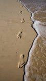 Pegadas na areia com ondas Fotografia de Stock
