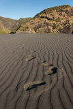 Pegadas na areia vulcânica Fotos de Stock Royalty Free