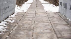 Pegadas no passeio nevado, primeira neve do ano Fotografia de Stock