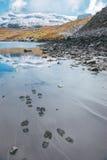 Pegadas perto de um lago da montanha em cumes franceses Imagens de Stock