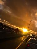 Pegado en tráfico de la puesta del sol en hogar de la manera Imagen de archivo
