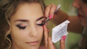 Pegan a la novia con las pestañas falsas Maquillaje profesional para la mujer con la piel joven sana de la cara almacen de video