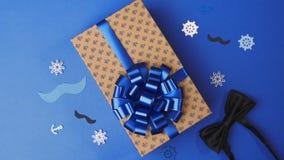 Pegando el arco a la actual caja para los hombres, envolviendo el presente, decoración del paquete, caja con los presentes metrajes