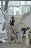 pegasus Concours hippique international Cavalier féminin sur un cheval blanc Ailes blanches Photo libre de droits