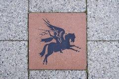 Pegasus på en belägga med tegel som firar minnet av den 1st brittiska luftburna uppdelningen Fotografering för Bildbyråer