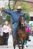 The Pegasus Parade 2018. Louisville, Kentucky, USA - May 03, 2018: The Pegasus Parade, African American man riding a horse down w broadway during the parade royalty free stock photography