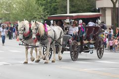 The Pegasus Parade 2018. Louisville, Kentucky, USA - May 03, 2018: The Pegasus Parade, Man and woman riding a carriage pulled by horses down W Broadway royalty free stock photo