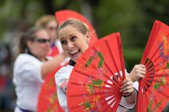 The Pegasus Parade 2018. Louisville, Kentucky, USA - May 03, 2018: The Pegasus Parade, Women in martial Arts uniforms with hand held fans, walking down W stock photos