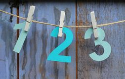 1, 2 , 3 pegged onto string. Paper cut numbers one, two and three pegged onto string on a blue painted wooden barn door , shades of blue stock photos