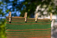 Pegged striped towel. Red and green striped towel pegged to a clothesline with four clothespins. Place for copy text Royalty Free Stock Photography