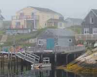 Peggy`s Cove in the fog. Peggy`s Cove B&B and old wooden pier in the fog at the harbor in Peggy`s Cove, Nova Scotia royalty free stock image