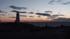 Peggys Cove Nova Scotia Sunset. Peggy`s Cove Lighthouse in Nova Scotia is one of the most iconic lighthouses in Canada. Capturing it at sunset is an absolute stock footage