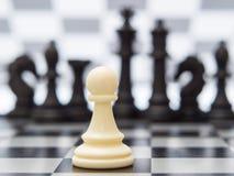 Pegno bianco contro lo sfondo dei pezzi degli scacchi scuri fotografie stock libere da diritti