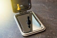 Pegno nero ordinario che guarda nello specchio e che vede re q dell'oro fotografia stock