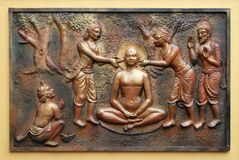 The pegs are being extracted with the help incers. Street bass relief on the wall of Jain Temple also called Parshwanath Temple in Kolkata, West Bengal, India Stock Image
