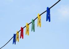Pegs de roupa coloridos que penduram na linha fio Fotografia de Stock Royalty Free