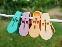 Pegs ou pregadores de roupa coloridos de roupa que penduram na corda branca Fotografia de Stock Royalty Free