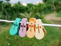 Pegs ou pregadores de roupa coloridos de roupa que penduram na corda branca Imagem de Stock Royalty Free