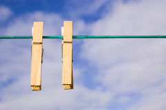 Pegs on a washing line. Two wooden clothes pegs sit on a washing line Stock Photo