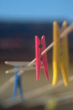 Pegs and washing line. Multi-coloured pegs clipped to a washing line Stock Photos