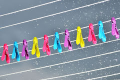 Pegs on a washing line in the rain. Colourful pegs on a washing line during a rain shower Royalty Free Stock Images