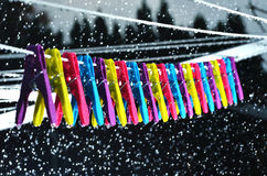 Pegs on a washing line in the rain. Colourful pegs on a washing line during a rain shower Stock Photography