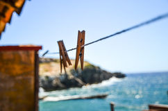 Pegs on a washing line by the sea. Soft focus photograph of ordinary laundry and household items to highlight a linear perspective feel against the blue Stock Photo
