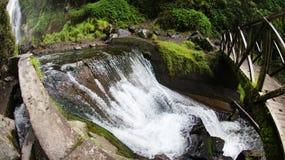 Peguche waterfall. And wooden  bridge through fisheye lense in Otavalo, Ecuador Stock Image