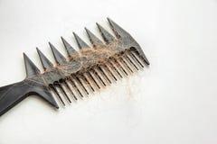 Peigne avec les cheveux perdus sur la table légère Photo libre de droits