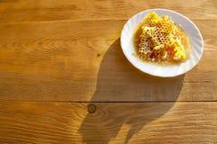 Peigne de miel sur une soucoupe blanche Image stock