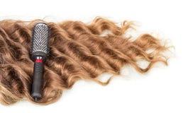 Peigne et mèches des cheveux bouclés d'isolement sur le blanc Photographie stock