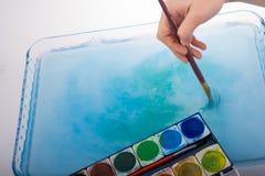 Peignez la dissolution comme la brosse de peinture touche l'eau Photo libre de droits