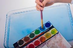 Peignez la dissolution comme la brosse de peinture touche l'eau Images stock
