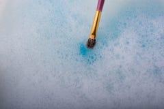 Peignez la dissolution comme la brosse de peinture touche l'eau Image stock
