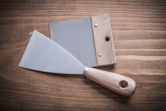 Peignez le spattle de grattoir et de mastic sur le conseil en bois Photos stock