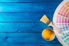 Peignez les boîtes palette de couleurs, boîtes ouvertes avec des brosses sur la table bleue Images stock
