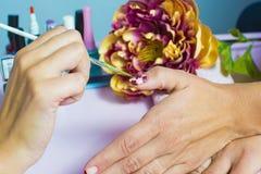Peignez les clous dans le salon de beauté image libre de droits