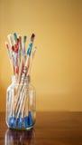 Peignez les pinceaux souillés dans le pot clair Photographie stock