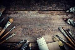 Peignez les tubes, les brosses pour peindre et les couteaux de palette sur le vieux fond en bois Image stock