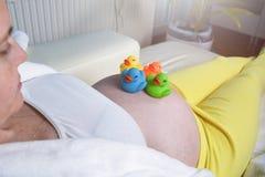Peignoir blanc de port de femme enceinte d?tendant et se reposant ? la maison sur un divan blanc photos stock