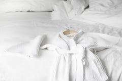 Peignoir blanc sur le lit dans la chambre d'hôtel Photographie stock libre de droits